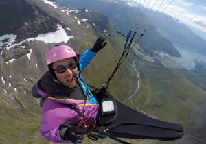 Åsmund Rognerud Birkeland henger høyt i en paraglider, over fjell og fjord