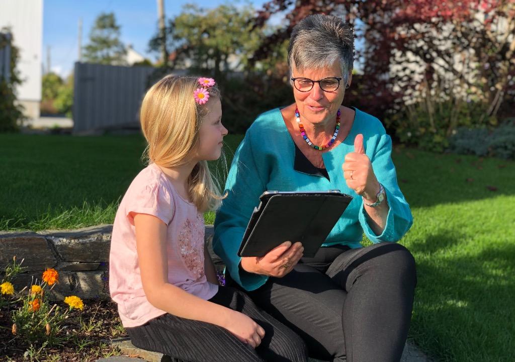 Ingrid Ask viser Aski Raski til elev, på nettbrett