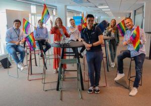 Uy Tran sammen med kollegaer fra Webstep som holder regnbueflagg